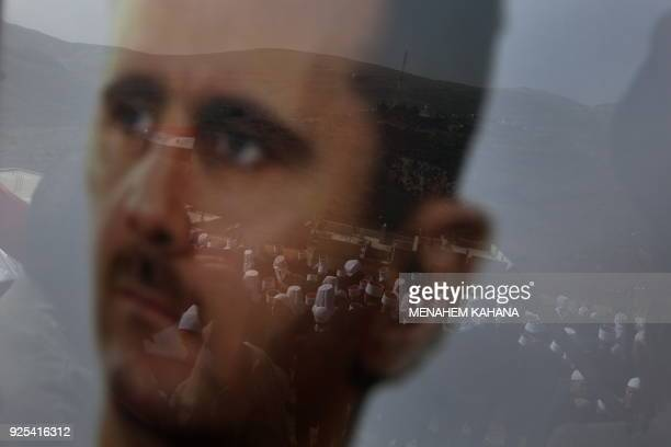 Druze residents of the Golan Heights are seen through a picture of Syrian Preident Bashar alAssad during a rally in the Druze village of Majdal Shams...