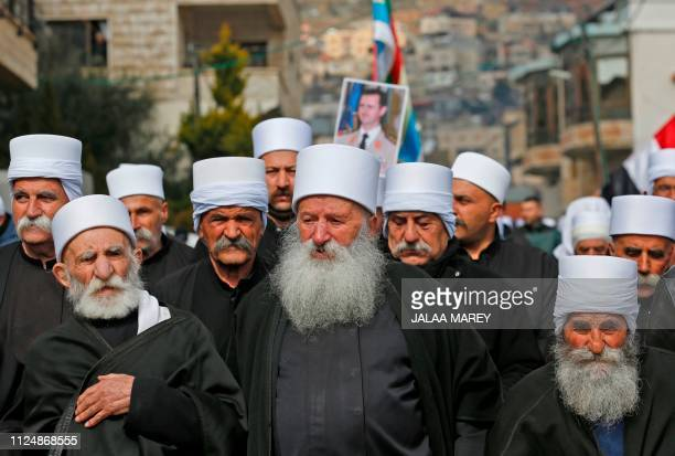 Druze residents of the Golan Heights carry a portrait of Syrian President Bashar alAssad during a rally in the village of Majdal Shams in the...