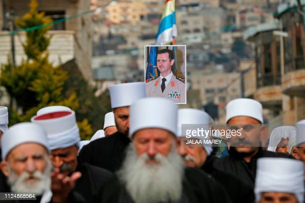 TOPSHOT Druze residents of the Golan Heights carry a portrait of Syrian President Bashar alAssad during a rally in the village of Majdal Shams in the...