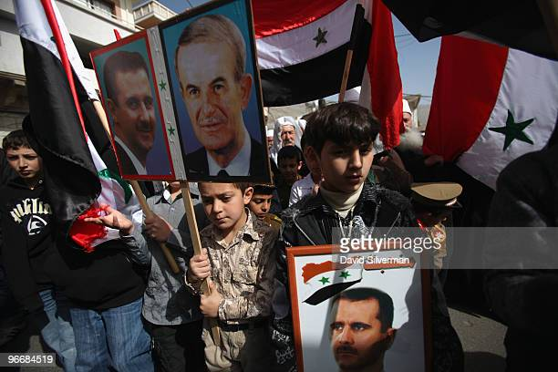 Druze residents of the Golan Heights hold Syrian flags and portraits of Syria's President Bashar alAssad and his late father Hafez alAssad during a...