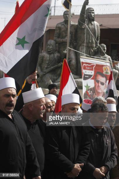 Druze residents of the Golan Heights hold the Syrian flag and a portrait of President Bashar alAssad during a rally in the village of Majdal Shams on...