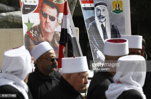 Druze residents of the Golan Heights hold the Syrian flag and portraits of President Bashar alAssad and late Arab Druze leader Sultan alAtrash during...
