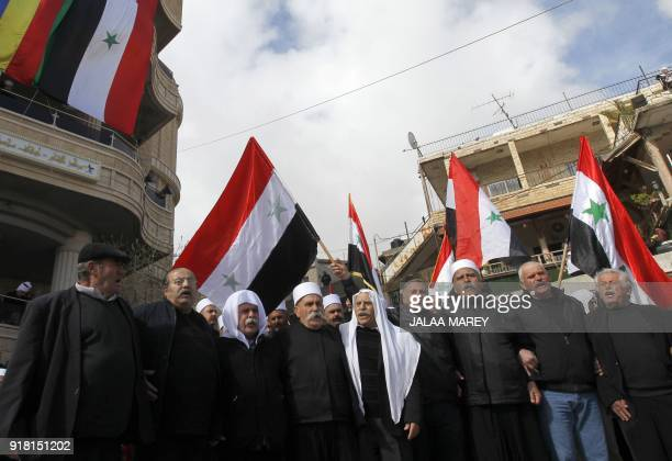 Druze residents of the Golan Heights hold the Syrian flag during rally in the Druze village of Majdal Shams on February 14 2018 to protest against...