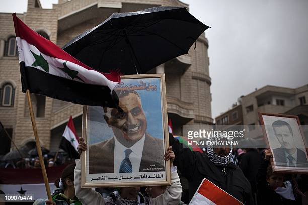 Druze residents of the Golan Heights march with a poster of late Egyptian president Gamal Abdel Nasser and Syria's President Bashar alAssad during a...