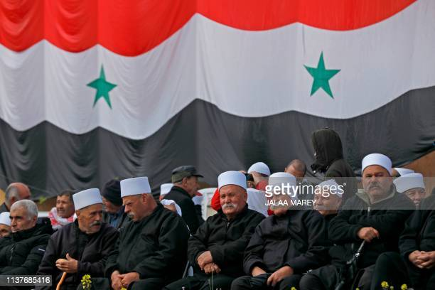 Druze residents of the Israeliannexed Golan Heights gather under a huge Syrian national flag during a rally held in the Druze village of Majdal Shams...