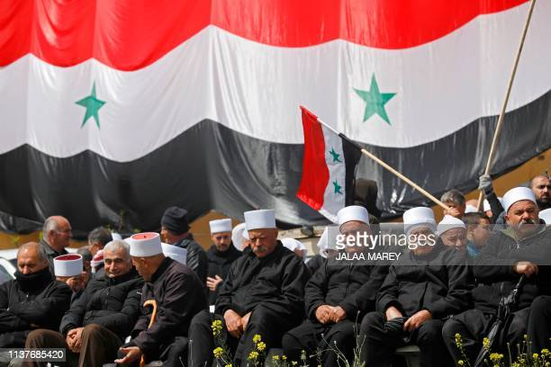 Druze residents of the Israeli-annexed Golan Heights gather under a huge Syrian national flag during a rally held in the Druze village of Majdal...