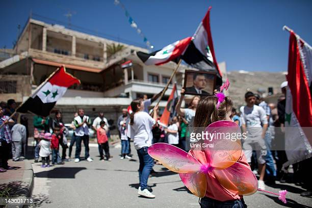 Druze residents of the the Israeli-occupied Golan Heights hold Syrian flags and portraits of Syria's President Bashar al-Assad, during a rally on...