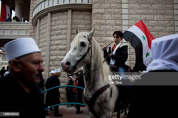 Druze youth, on horseback, waves the Syrian flag during a rally in the village of Majdel Shams, near the border between Israel and Syria on February...