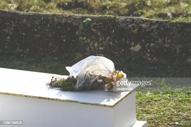 dry bouquet on a grave - tombstone stock pictures, royalty-free photos & images
