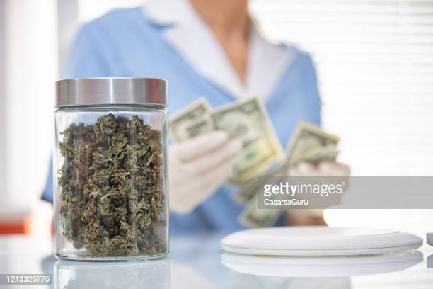 dry cannabis buds in a jar in cannabis store - cannabis store stock pictures, royalty-free photos & images