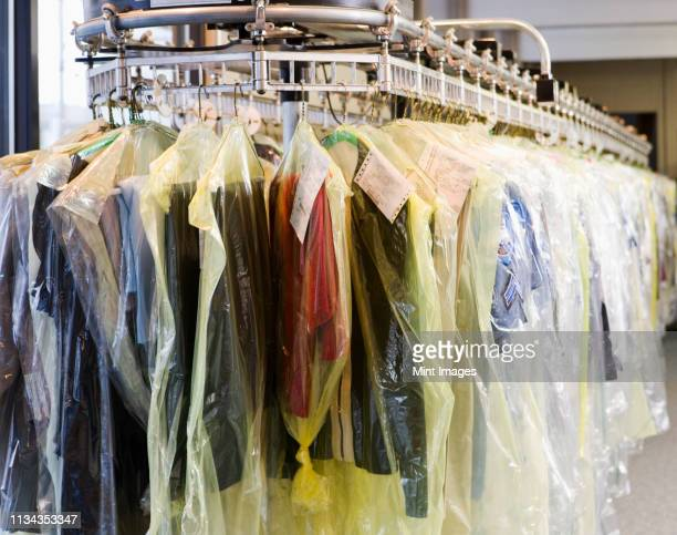 dry cleaning wrapped in plastic on rack - dry cleaner stock pictures, royalty-free photos & images