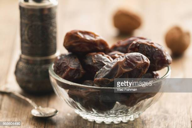 dry dates on a bowl on a vintage or rustic table top wood background - ramadan stock pictures, royalty-free photos & images
