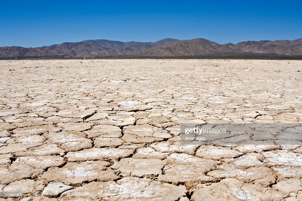 A dry lakebed landscape in front of mountains under blue sky : Stock Photo