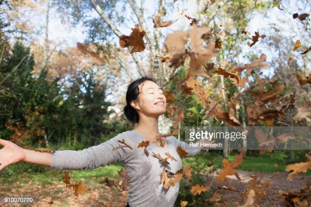 Dry leaves falling on happy woman standing with arms outstretched at park during autumn