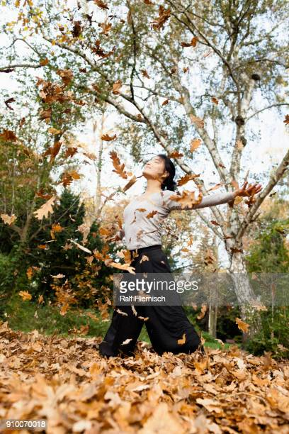 Dry leaves falling over young woman standing on field against trees at park