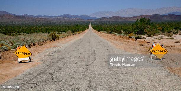 "dry road in desert with ""flooded"" signs - timothy hearsum stock pictures, royalty-free photos & images"