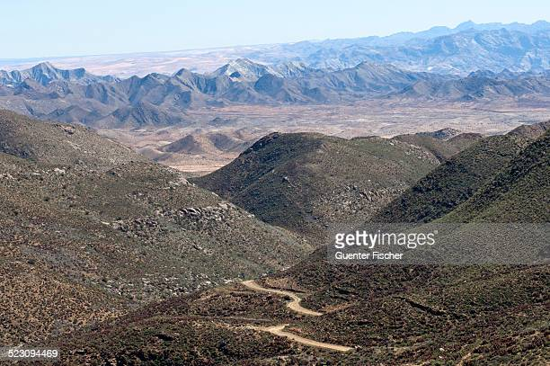 dry valley with road in a karoo landscape at helskloof pass, richtersveld national park, namaqualand, northern cape province, south africa, africa - ナマクワランド ストックフォトと画像