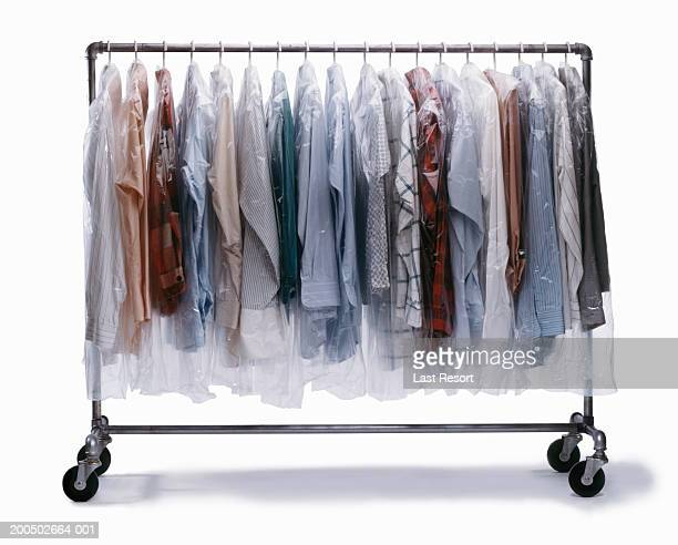 dry-cleaned clothes wrapped in plastic hanging on clothes rack - dry cleaned stock pictures, royalty-free photos & images