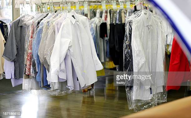 drycleaned clothing moving along rack - dry cleaner stock pictures, royalty-free photos & images