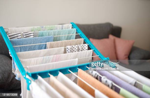 drying laundry on drying rack in a small living room - tumble dryer stock pictures, royalty-free photos & images