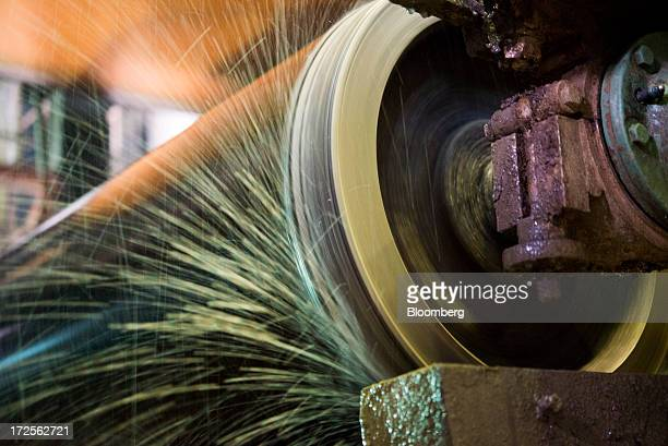 A drying roller sprays excess water as it collects paper fiber while making a new roll of paperboard at Newark Recycled Paperboard Solutions in...