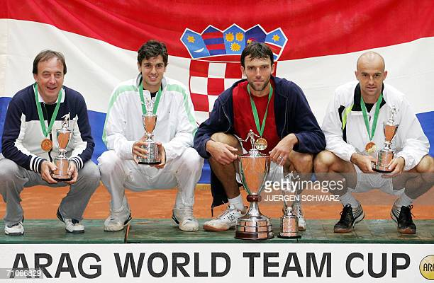 Croatia's trainer Riccardo Piatti and his tennis players Mario Ancic Ivo Karlovic and Ivan Ljubicic celebrate with their trophy after the final...