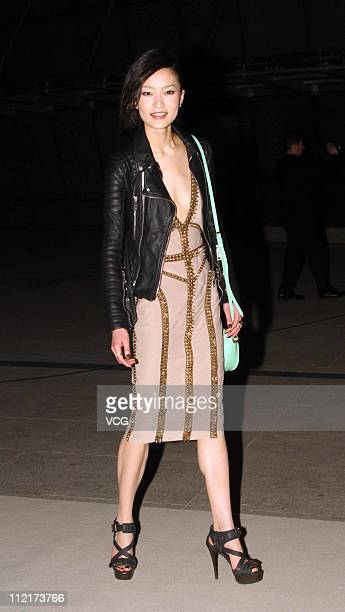 Du Juan poses for photos as she arrives at the corporate event of the fashion apparel company Burberry at Sparkle Roll Plaza on April 13 2011 in...