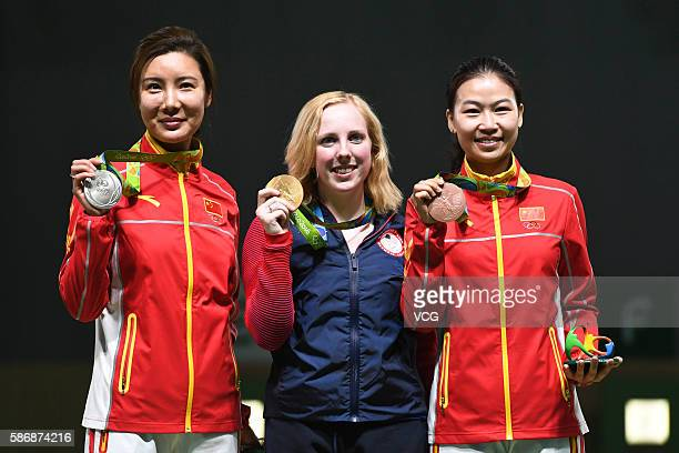 Du Li of China with silver Virginia Thrasher of the United States with gold and Yi Siling of China with bronze pose on the podium following the...