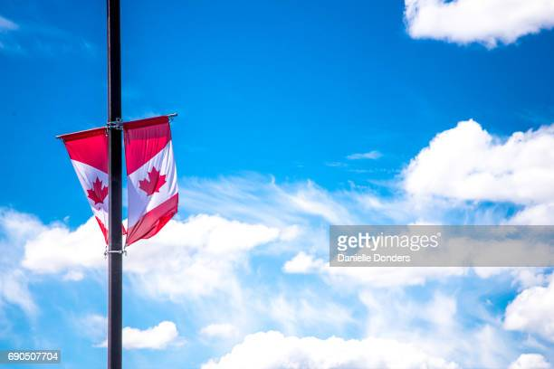 Dual Canadian flags on a pole against a blue sky with clouds