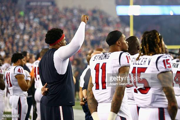 Duane Brown of the Houston Texans raises his fist during the national anthem before the game against the New England Patriots at Gillette Stadium on...