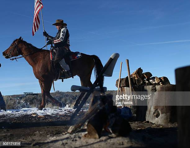 Duane Ehmer carries an American flag as he rides his horse Hellboy at the occupied Malheur National Wildlife Refuge on January 15 2016 near Burns...