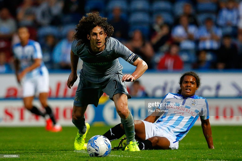 Duane Holmes of Huddersfield in action with Fabricio Coloccini (L) of Newcastle during the Pre Season Friendly match between Huddersfield Town and Newcastle United at the John Smith's Stadium on August 5, 2014 in Huddersfield, England.