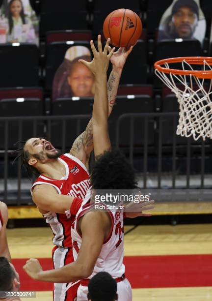 Duane Washington Jr. #4 of the Ohio State Buckeyes attempts a layup as Ron Harper Jr. #24 of the Rutgers Scarlet Knights defends during the first...
