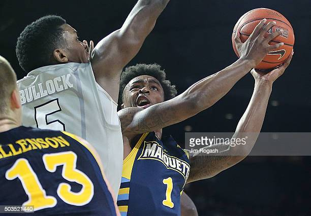 Duane Wilson of the Marquette Golden Eagles scores the winning basket against the defense of Rodney Bullock of the Providence Friars in the second...