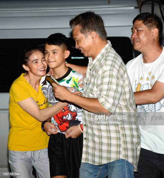 Duangpetch Promthep a member of rescued football team 'Wild Boars' is welcomed by his family members on arrival at his home after attending a press...