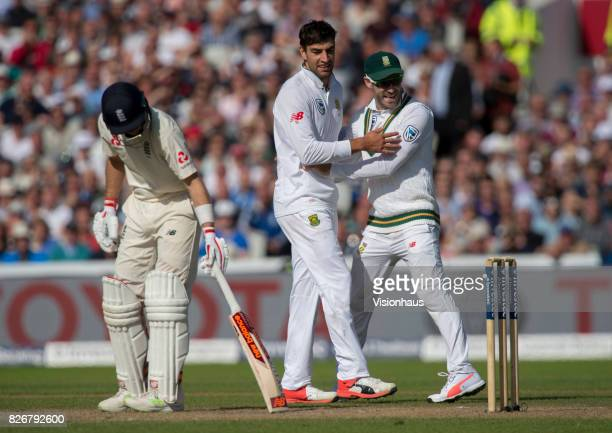 Duanne Olivier is congratulated by his captain Faf Du Plessis after trapping Joe Root LBW batting during the first day of the fourth test between...