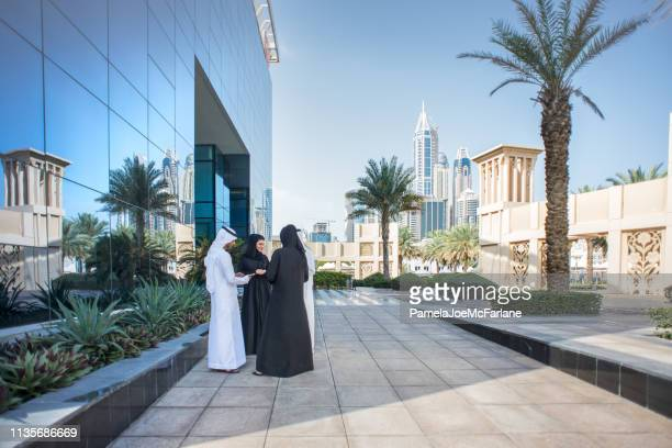 dubai businessmen and businesswomen having meeting outside modern office building - gulf countries stock pictures, royalty-free photos & images