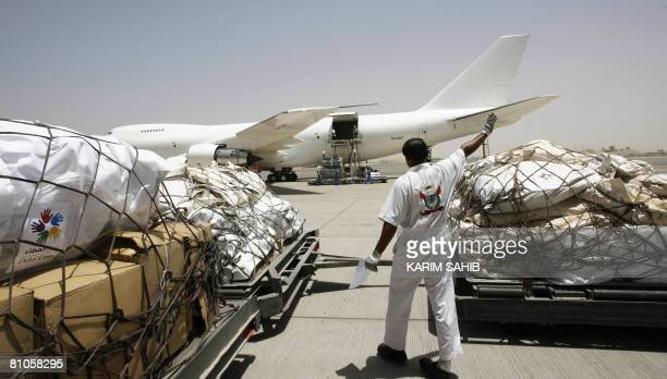 A 'Dubai Cares' worker stands with aid from Dubai at Yangon International Airport for victims of Cyclone Nargis early morning on May 12 2008 The...