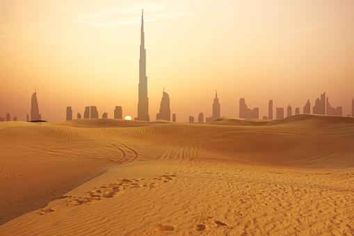 Dubai city skyline at sunset seen from the desert 958713512