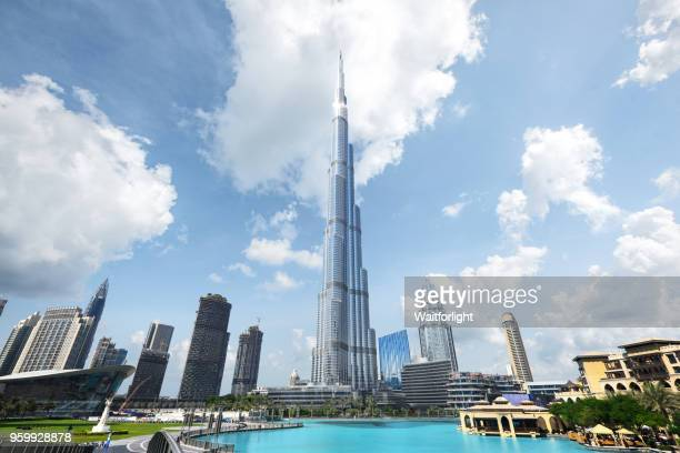 dubai downtown district against cloud sky - burj khalifa stock photos and pictures