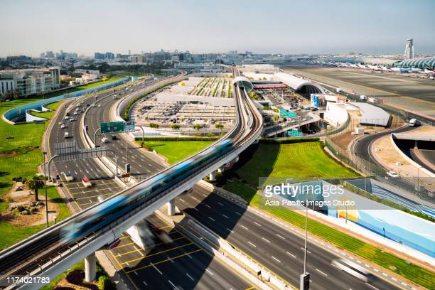 dubai international airport and metro at sunny day. - dubai stock pictures, royalty-free photos & images