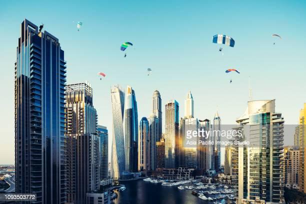 ドバイ マリーナ スカイラインと夜明けに活動を楽しいパラシュート - スカイダイビング ストックフォトと画像