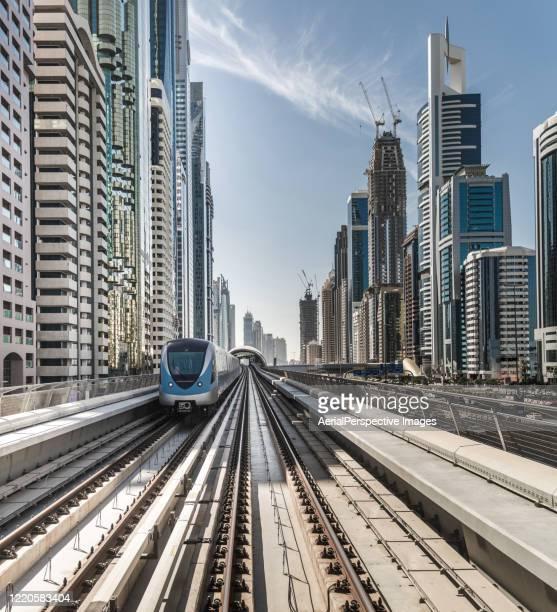 dubai metro passes through the city - vanishing point stock pictures, royalty-free photos & images