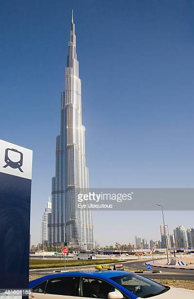 UAE Dubai Metro sign and taxi in front of Burj Khalifa tower
