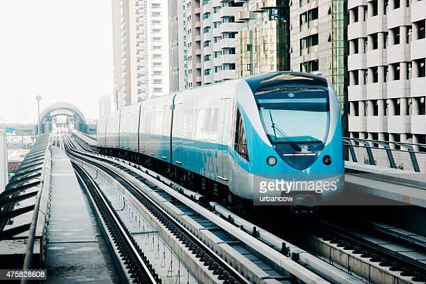 Dubai metro train with apartment buildings, daytime, nobody