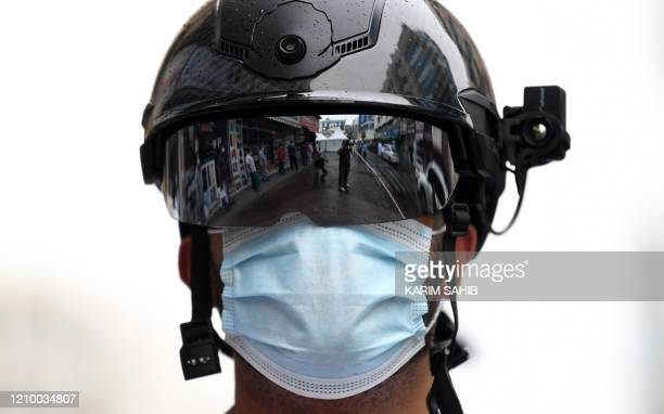 A Dubai policeman wearing a helmet equipped with a temperature camera stands outside a testing center for COVID19 in the Naif area of the Gulf...