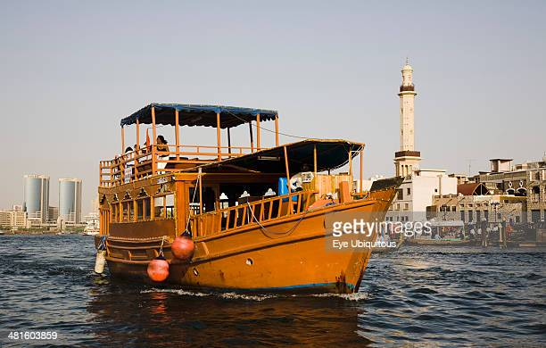 UAE Dubai restored traditional boat taking tourists on the Creek with Twin Towers shopping mall and skyline behind