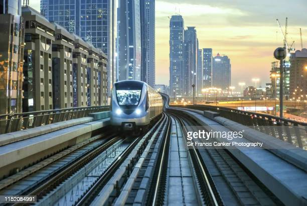 dubai skyline illuminated at sunset with driverless metro train approaching fast, uae - autonomous technology stock pictures, royalty-free photos & images