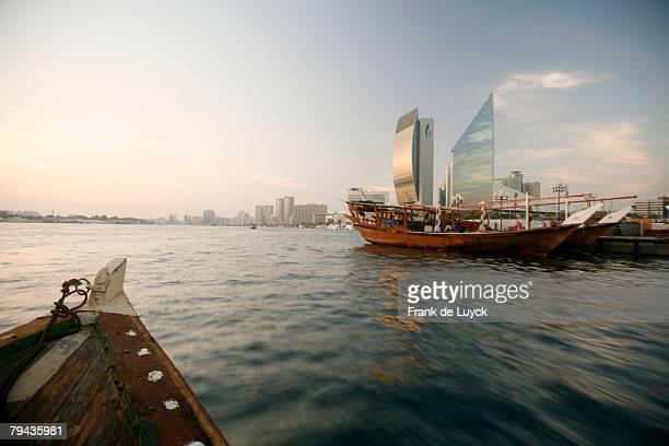 Dubai skyline photographed from an abra sailing in Dubai Creek. Traditional dhows can be seen moored alongside quays. Dubai Creek, Dubai, United Arab Emirates