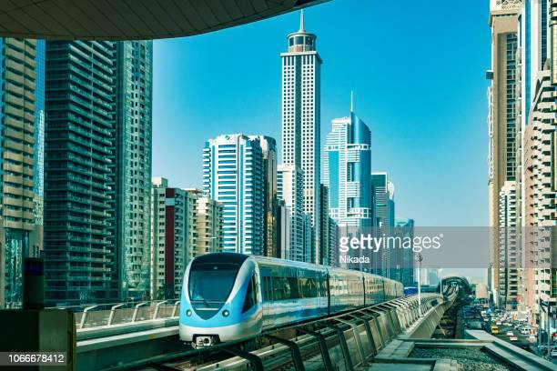 dubai skyline with metro - rail transportation stock pictures, royalty-free photos & images